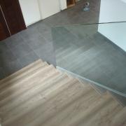 Escalera revestida en madera. Barandilla acristalada Ronda Molí